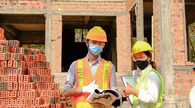 Equipe do empreiteiro do engenheiro reunindo-se com o projeto do setor de plano de segurança do trabalho e verificando o projeto no local de construção.
