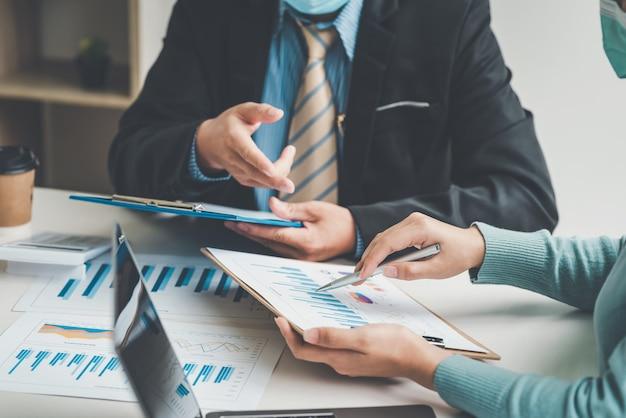 Equipe do empresário sentados juntos na reunião de brainstorming do escritório segurando uma caneta apontando para o gráfico no escritório.