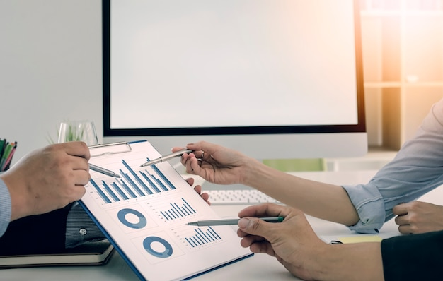 Equipe do negócio que analisa a carta e os gráficos da renda.