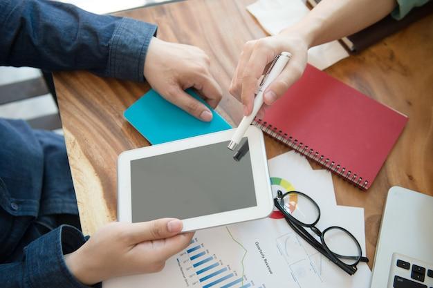Equipe do negócio que informa a estratégia de marketing com o escritório da tabuleta em casa.