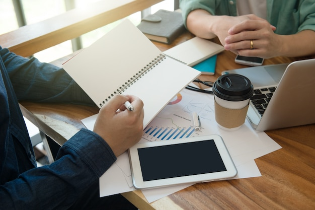 Equipe do negócio que informa a estratégia de marketing com o livro de nota no escritório domiciliário.