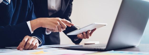Equipe do negócio que usa a tabuleta e o laptop para trabalhar no escritório.