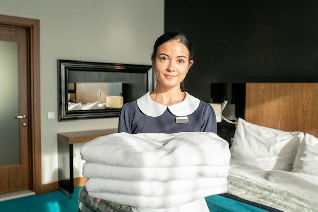 Equipe do serviço de quarto feliz segurando uma pilha de lençóis brancos limpos no quarto