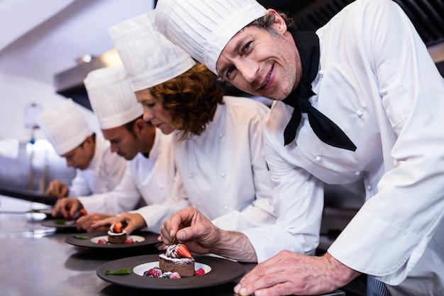 Equipe dos cozinheiros chefe que termina pratos de sobremesa
