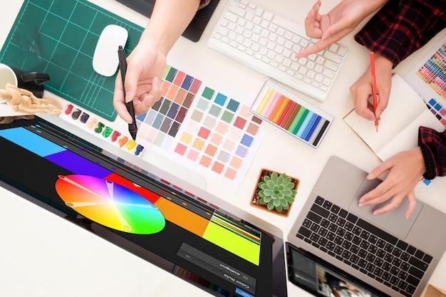Equipe dos designer gráficos que trabalham em um computador no estúdio criativo do projeto da ocupação dos officeideas, local de trabalho do artista com vista superior.
