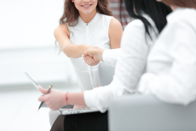 Equipe e aperto de mão de negócios de duas mulheres no escritório.