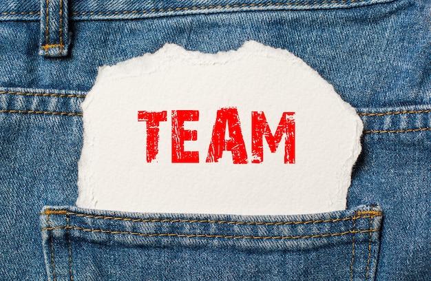 Equipe em papel branco no bolso da calça jeans azul