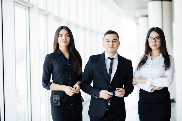 Equipe em pé na sala do escritório, líder da equipe na frente. os empresários caminham no corredor do escritório sob o sol