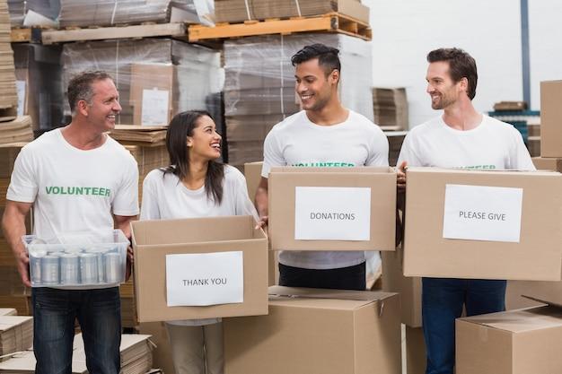 Equipe feliz de voluntários segurando caixas de doações