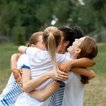 Equipe feliz se abraçando ao ar livre