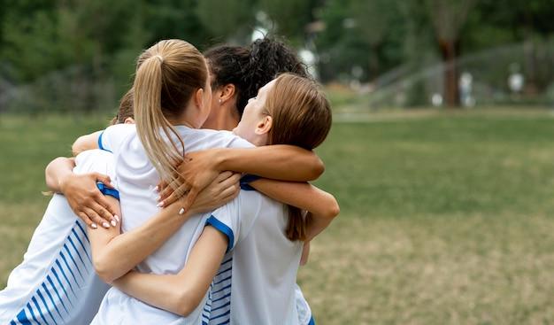 Equipe feliz se abraçando no campo