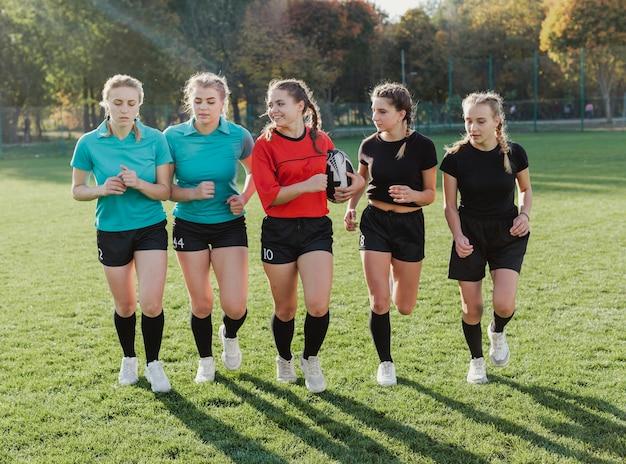Equipe feminina de rugby, correndo com uma bola