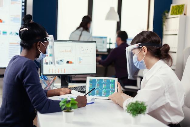 Equipe financeira de uma grande empresa fazendo análise financeira usando máscara durante covid19. grupo diversificado de empresários trabalhando e se comunicando juntos no escritório com novos padrões, respeitando s