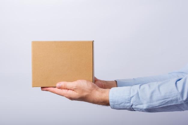 Equipe guardar a caixa no comprimento do braço na parede branca. caixa de papelão quadrada. entrega de encomendas. vista lateral.