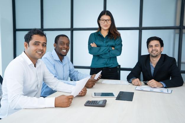 Equipe internacional bem sucedida positiva que guarda a análise de negócio na reunião.