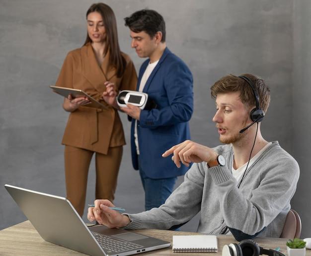 Equipe jovem de pessoas usando laptop e fone de ouvido de realidade virtual
