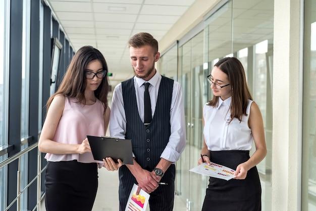 Equipe jovem dos sonhos de três empresários profissionais que discutem a papelada no corredor de um escritório moderno