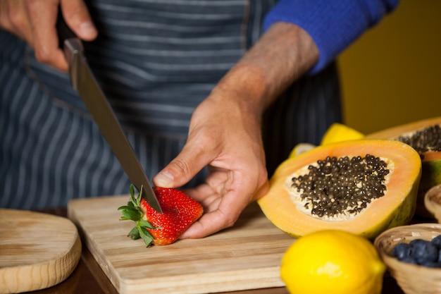 Equipe masculina cortando morango na seção orgânica