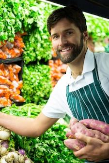 Equipe masculina organizando legumes na seção orgânica