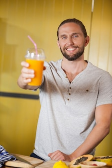 Equipe masculina segurando copo de suco de laranja na seção orgânica