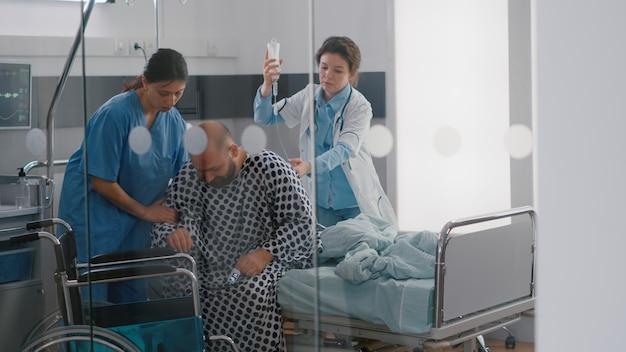 Equipe médica ajudando paciente doente com fratura por lesão na perna ao colocar a cadeira de rodas