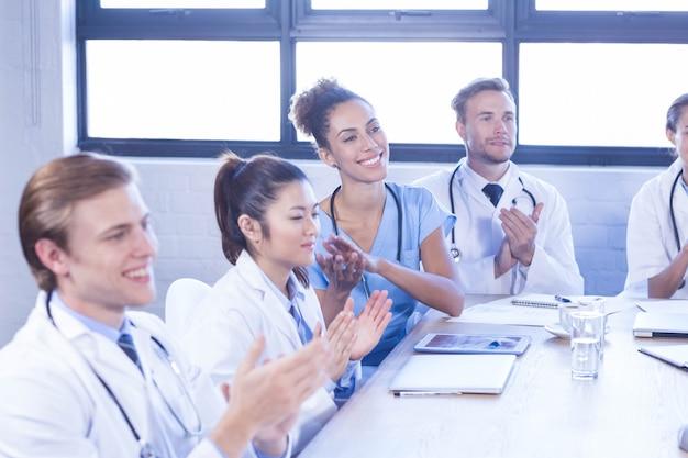 Equipe médica aplaudindo e sorrindo em reunião na sala de conferências
