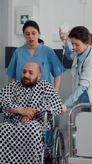 Equipe médica auxilia paciente doente com fratura na perna colocando-se em cadeira de rodas em fisioterapia se recuperando em enfermaria de hospital