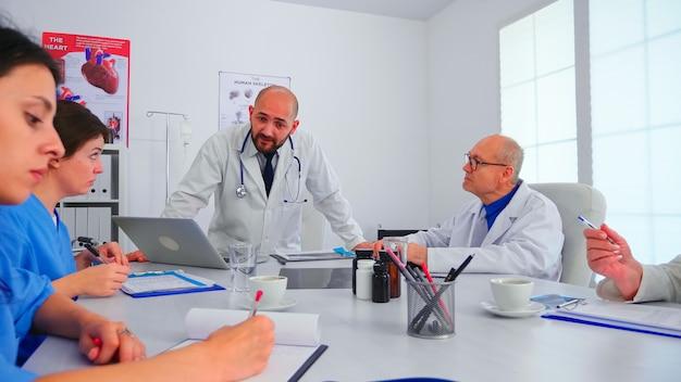 Equipe médica, conversando com o profissional da equipe de trabalho em equipe, vestindo jaleco branco na sala de reuniões do hospital. terapeuta clínico com colegas falando sobre doença, especialista, especialista, comunicação.