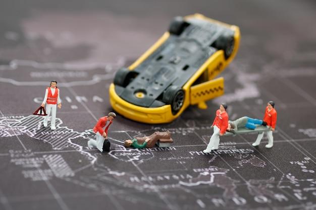 Equipe médica de emergência em miniatura para ajudar pessoas acidente de carro.