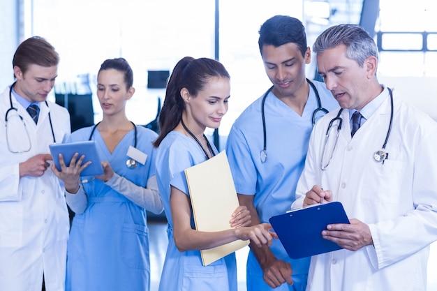 Equipe médica discutindo a papelada na área de transferência no hospital