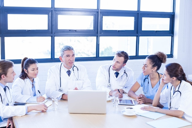 Equipe médica discutindo em reunião em uma sala de conferências