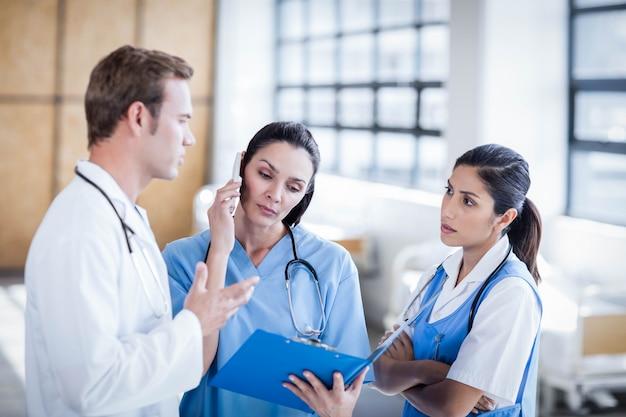 Equipe médica discutindo o relatório juntos no hospital