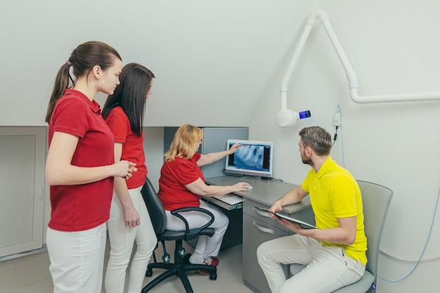 Equipe médica do dentista no consultório odontológico discute e examina a imagem do raio x olhando para o computador