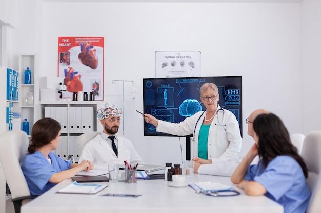 Equipe médica do hospital fazendo pesquisa de atividade cerebral usando fone de ouvido com sensores