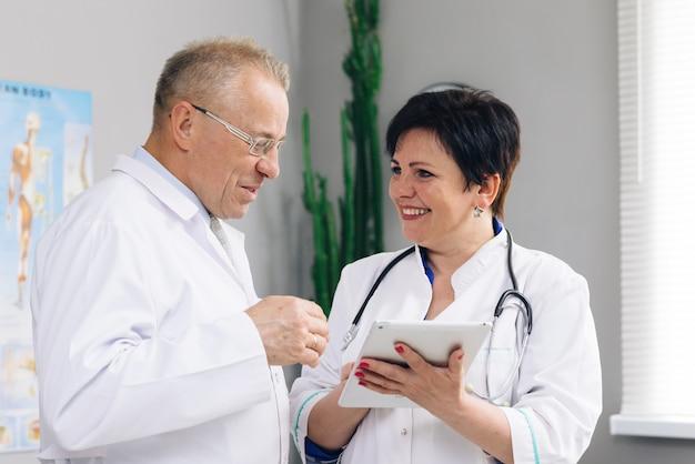 Equipe médica, dois homens e mulheres jovens médicos usam jalecos brancos conversam, usam tablet digital