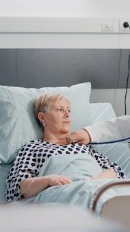 Equipe médica fazendo consulta de saúde para paciente idoso