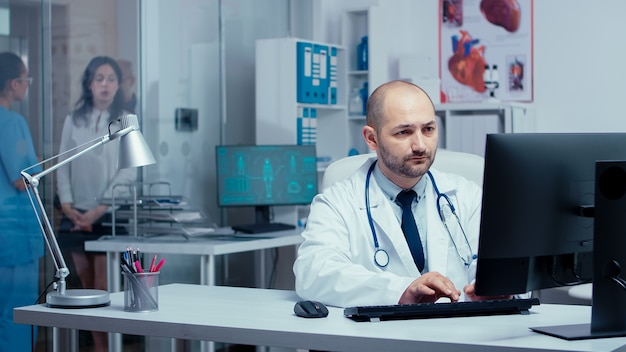 Equipe médica feliz sorrindo para a câmera. médico praticante trabalhando no pc enquanto a equipe médica e enfermeiras conversam com os pacientes por trás de paredes de vidro. especialista em sistema de saúde em hospital
