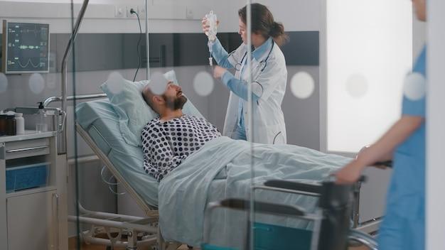 Equipe médica monitorando a freqüência cardíaca vital do paciente e ajudando com fluidos