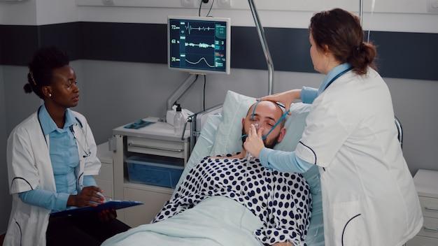 Equipe médica monitorando batimentos cardíacos de homem doente durante consulta respiratória
