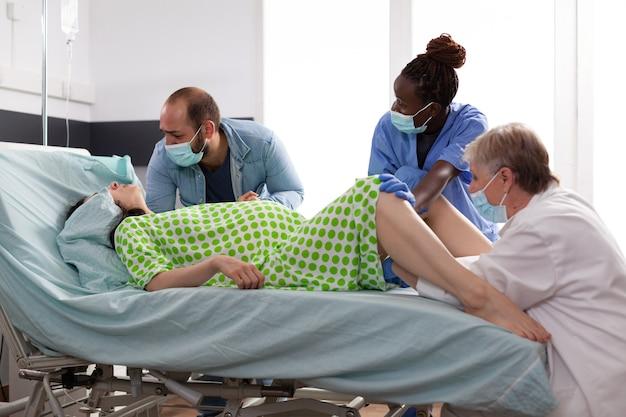 Equipe médica multiétnica auxiliando parto de mulher
