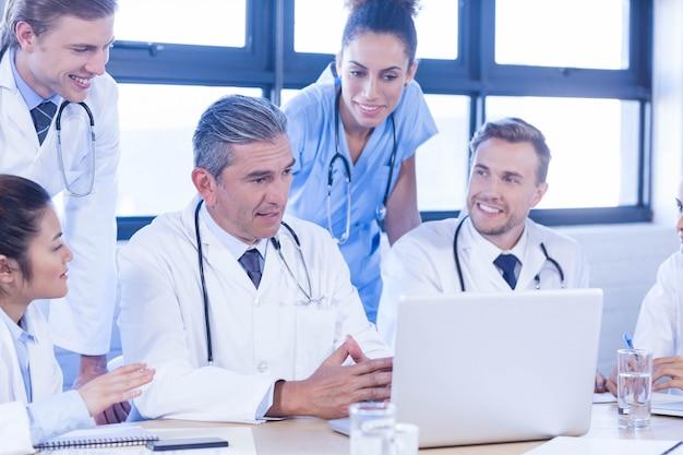 Equipe médica olhando para laptop e tendo uma discussão na sala de conferências