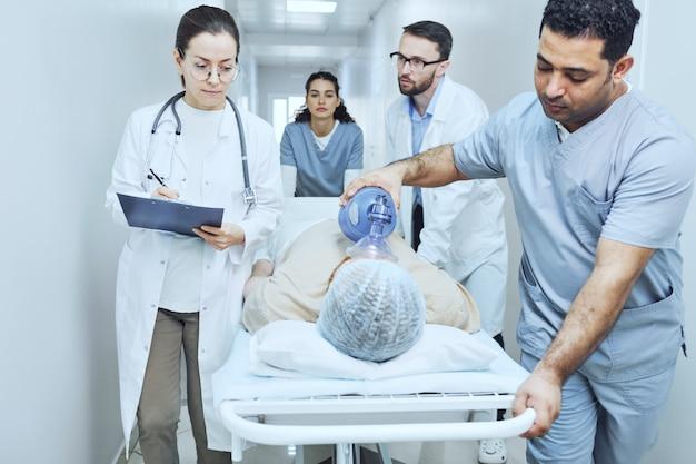Equipe médica realizando reanimação com desfibrilador ao paciente no hospital