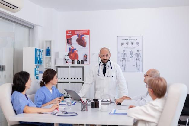 Equipe médica se reunindo na sala de conferências do hospital para planejar o tratamento de saúde
