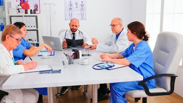 Equipe médica sentada e discutindo sobre o diagnóstico do paciente na sala de conferências do hospital. terapeuta especialista em clínica falando com colegas sobre doenças para desenvolvimento de tratamento, profissional de medicina