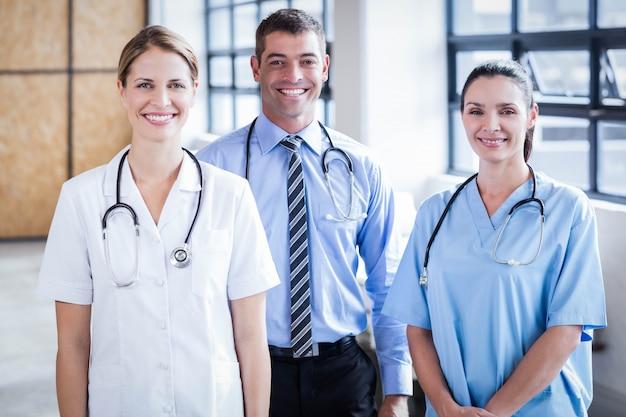 Equipe médica sorrindo para a câmera juntos no hospital