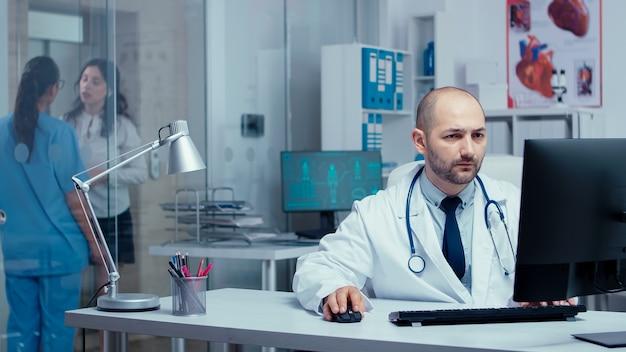 Equipe médica trabalhando em clínica privada moderna. médico praticante trabalhando no pc enquanto a equipe médica e enfermeiras conversam com os pacientes por trás de paredes de vidro. especialista em sistema de saúde em hospital