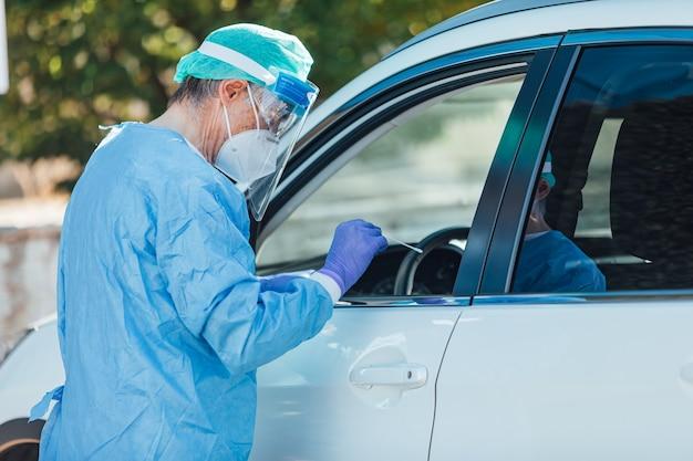 Equipe médica usando um epi, realizando pcr com um cotonete na mão, em um paciente dentro de seu carro para detectar se ele está infectado com covid-19