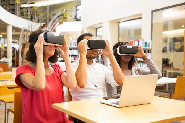 Equipe mista de corrida de estudantes adultos usando óculos de realidade virtual
