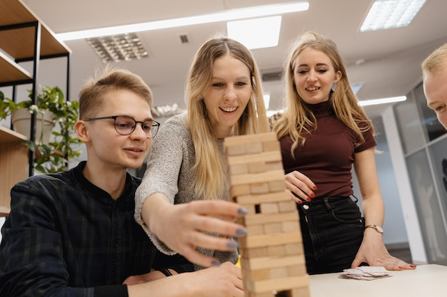 Equipe mista, jogando blocos de madeira jogo no escritório