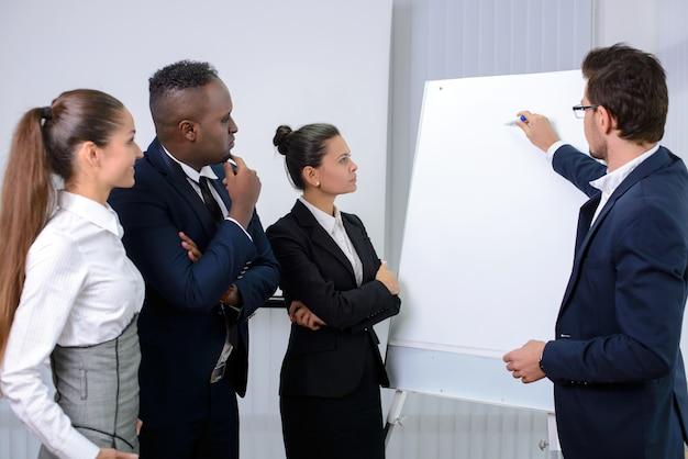 Equipe multi-étnica nova do negócio que planeia uma estratégia nova.